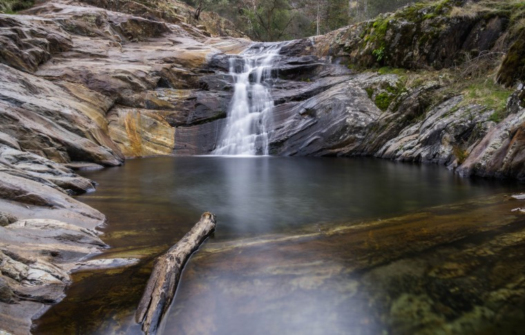 A small waterfall cascading over rocks and collecting in a pool
